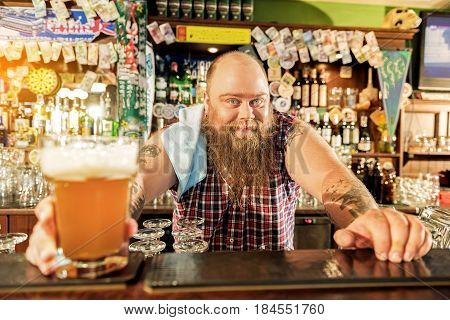 Portrait of happy bearded man standing at counter. He selling drinks in alehouse