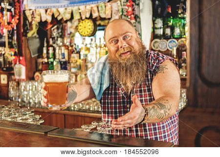 Here are your delicious ale. Cheerful bearded man showing cup of alcohol in dramshop