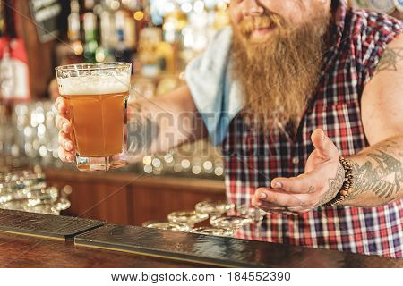 Focus on close up male arm with glass of beer in hand. He stretching out it in tap-room