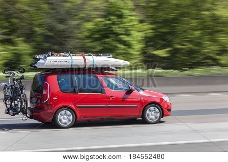 Frankfurt Germany - March 30 2017: Red Skoda Roomster packed with bikes and surfing stuff on the highway in Germany