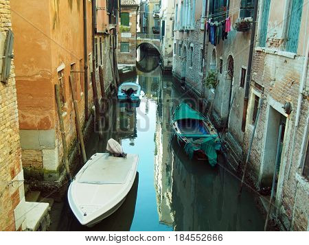 Quiet small canal in venice with bridge and boats