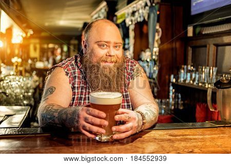 Portrait of bearded male expressing gladness while leaning on workplace. He drinking glass of beer in dramshop