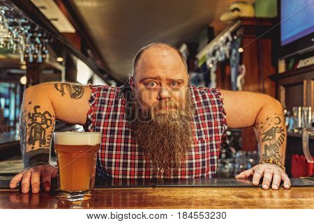 Portrait of fat bartender showing astonishment while standing at counter in alehouse
