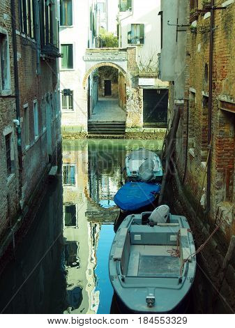 venice canal with reflected house and doorway windows and boats