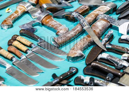 Hunting knives and knifes of large and small sizes lie on a table in a hunting and fishing store