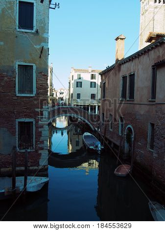 Venice old buidings alongside a small canal whith a bridge reflecting in the water boats and a blue sky