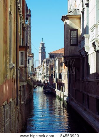 Venice old buildings alongside a small canal whith a bridge reflecting in the water boats and a blue sky