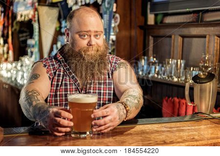 It is your order. Funny bearded male bartender giving glass of cold foamy beer. He standing at counter in dramshop