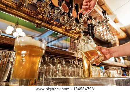 low angle of close up man hand filling glass of cold alcohol drink in dramshop