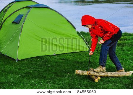 woman sawing wood for campfire using portable tourist saw. Active outdoor recreation during the camping holidays