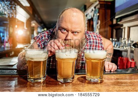Why are you looking at me. Bearded man expressing surprise while drinking bear in alehouse