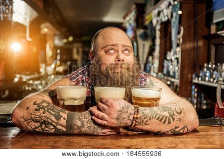 Ooh, this appetizing drink. Bearded man expressing wistfulness while hugging glasses of beer in boozer