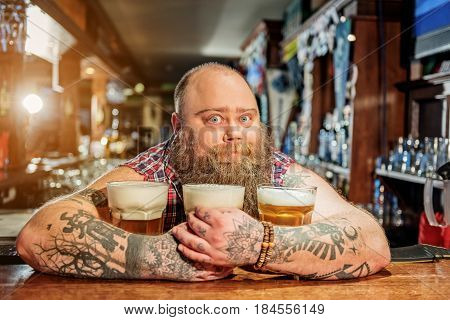 Portrait of fat male showing wonder while embracing mugs of alcohol beverage. He looking at camera