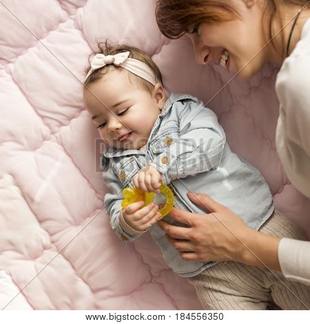 Top view of a mother and her adorable baby girl lying on the bed in bedroom smiling and playing. Focus on the baby