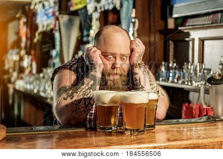 This delicious drink. How can I drink so lot of beverage. Fat man showing surprise while looking at alcohol in pub