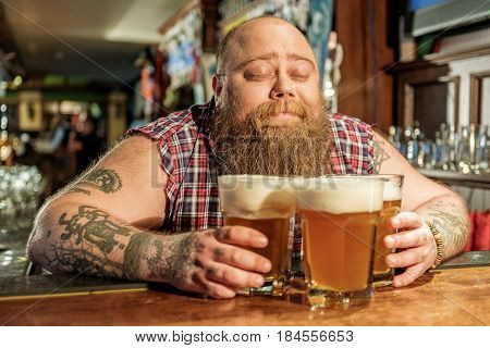 Bearded male expressing pleasant while sniffing glasses of beer in dramshop