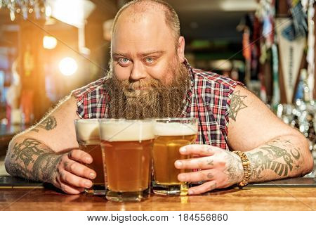 Portrait of fat male showing happiness while putting alcohol drink on table in tap-room