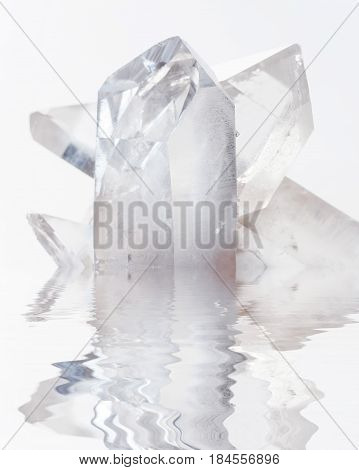 Cluster of several transparent quartz crystals close-up on a white background reflected in a water surface with small waves