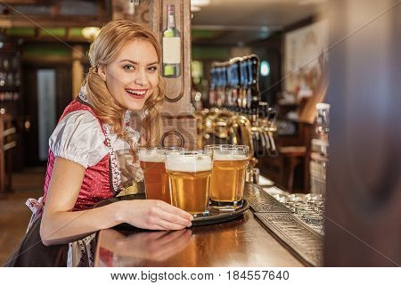 Portrait of woman demonstrating cheerfulness while holding tray with glasses of beer