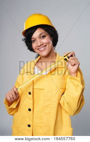 Renovation, building concept. Smiling mixed race construction woman wearing yellow protect helmet and overall holding measurement tape, over grey background