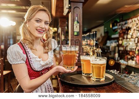 Portrait of woman showing gladness while keeping glass of cold foamy beer in pub