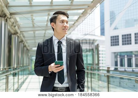 Business man holding cellphone and looking far away