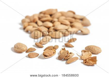 Lots of Almond nut in shell, shelled and some broken shells isolated on white background close up selective focuswith beautiful bokeh effect