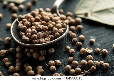 Coriander Dry Seeds In Metal Spoon On A Black Wooden Table, Horizontal, Selective Focus