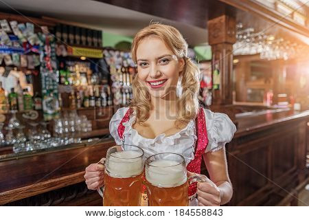 Portrait of woman expressing gladness while carrying big cups of foamy beer in dramshop