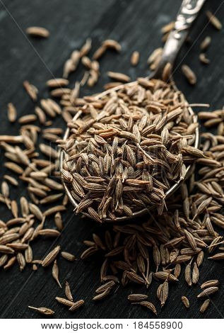 Cumin Seeds In Metal Spoon On A Wooden Table, Vertical