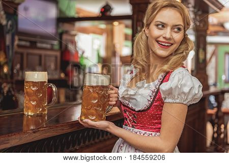 Portrait of girl expressing cheerfulness while caring glass of cold foamy bear in pub