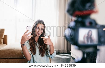 Young Woman Recording Her Video On Camera Mounted On Tripod.