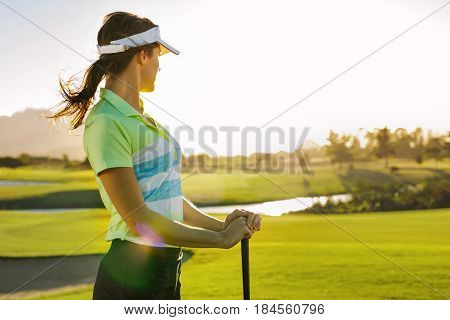 Professional female golfer holding golf club on field and looking away. Young woman standing on golf course on a sunny day.