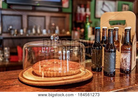 Cake and alcohol drinks situating on counter in modern pub