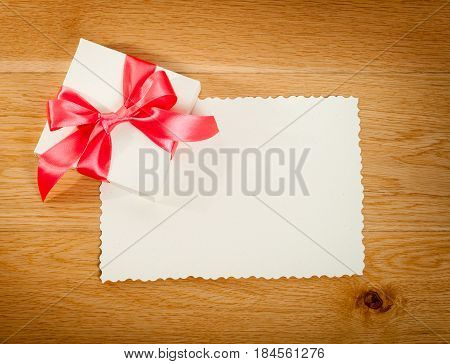 Gift box with blank gift tag on wooden background