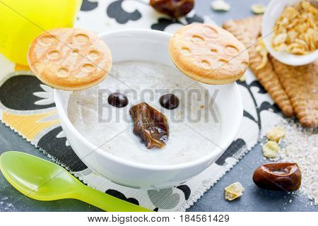 Oat bran porridge with cookies chocolate and dates shaped cute koala face for healthy breakfast
