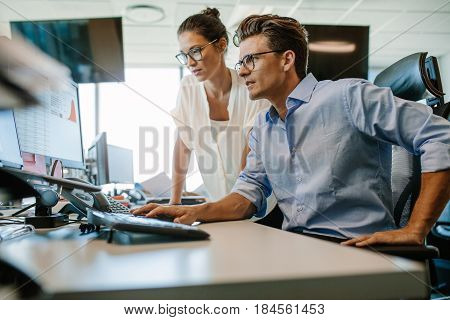 Shot of two business colleagues working in their office using a desktop computer. Man sitting at his desk with female colleague standing by.