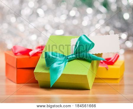 Bright gift boxes with ribbons and blank gift tag over silver background