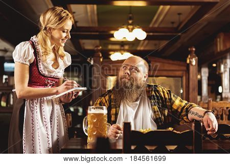cheerful female writing order of happy bearded fat man. He sitting at table in tap-room
