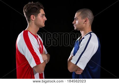 Two rival football player looking at each other against white background