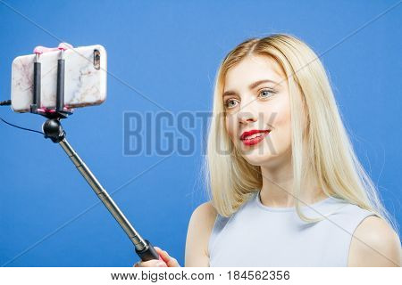 Pretty Blonde is Grimacing While Taking a Photo Using Selfie Stick on Blue Background. Cute Girl with Long Hair and Red Lips Photographing Herself by Smartphone in Studio, Closeup.