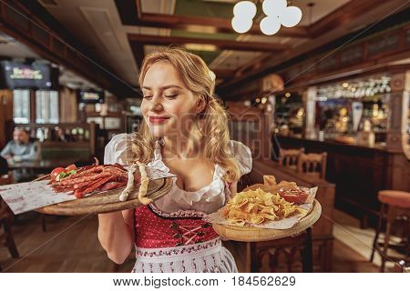 This delicious smell. Smiling waitress snuffing frankfurter while keeping them on tray in boozer