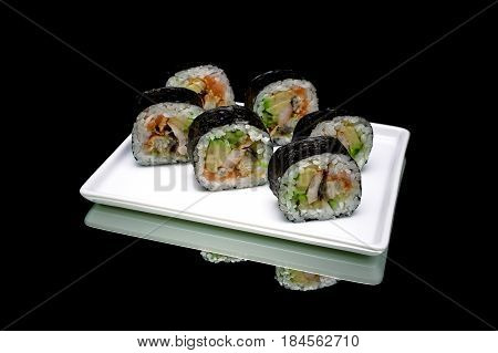 Rolls with eels and avocado on a white plate. Black background - horizontal photo.