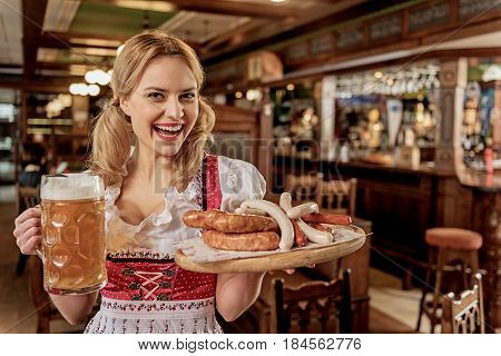 Portrait of outgoing young girl holding sausages and glass of cold foamy beer to client in dramshop