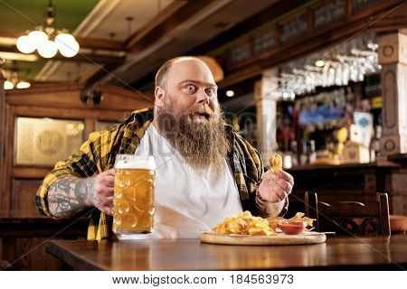 I am crazy for meal. Low angle funny fat male tasting potato chips and glass of cold beer in pub
