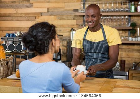 Happy male barista serving coffee to customer in coffee shop