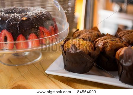 Close-up of muffins and cake on counter in coffee shop