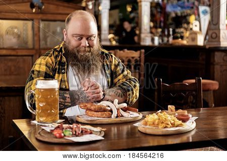 This appetizing food. Bearded overweight man expressing wish. He wanting to eat big portions of fat food and drinking alcohol in bar
