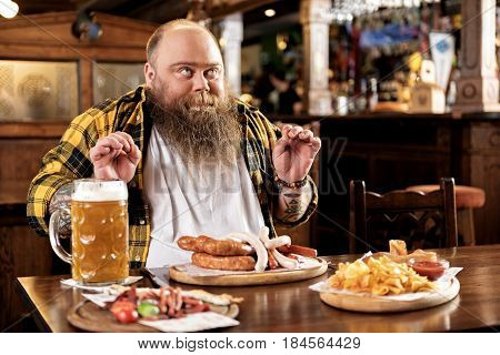 It is delicious meal. Fat male expressing gladness while tasting dish in pub
