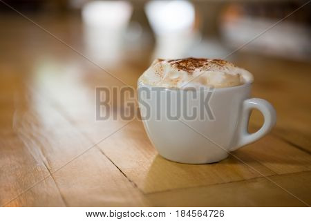 Close-up of coffee cup with creamy froth on wooden table in cafe